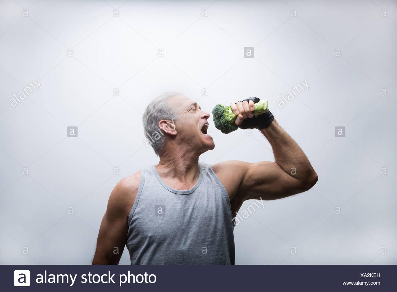 Senior uomo circa per mangiare i broccoli Immagini Stock