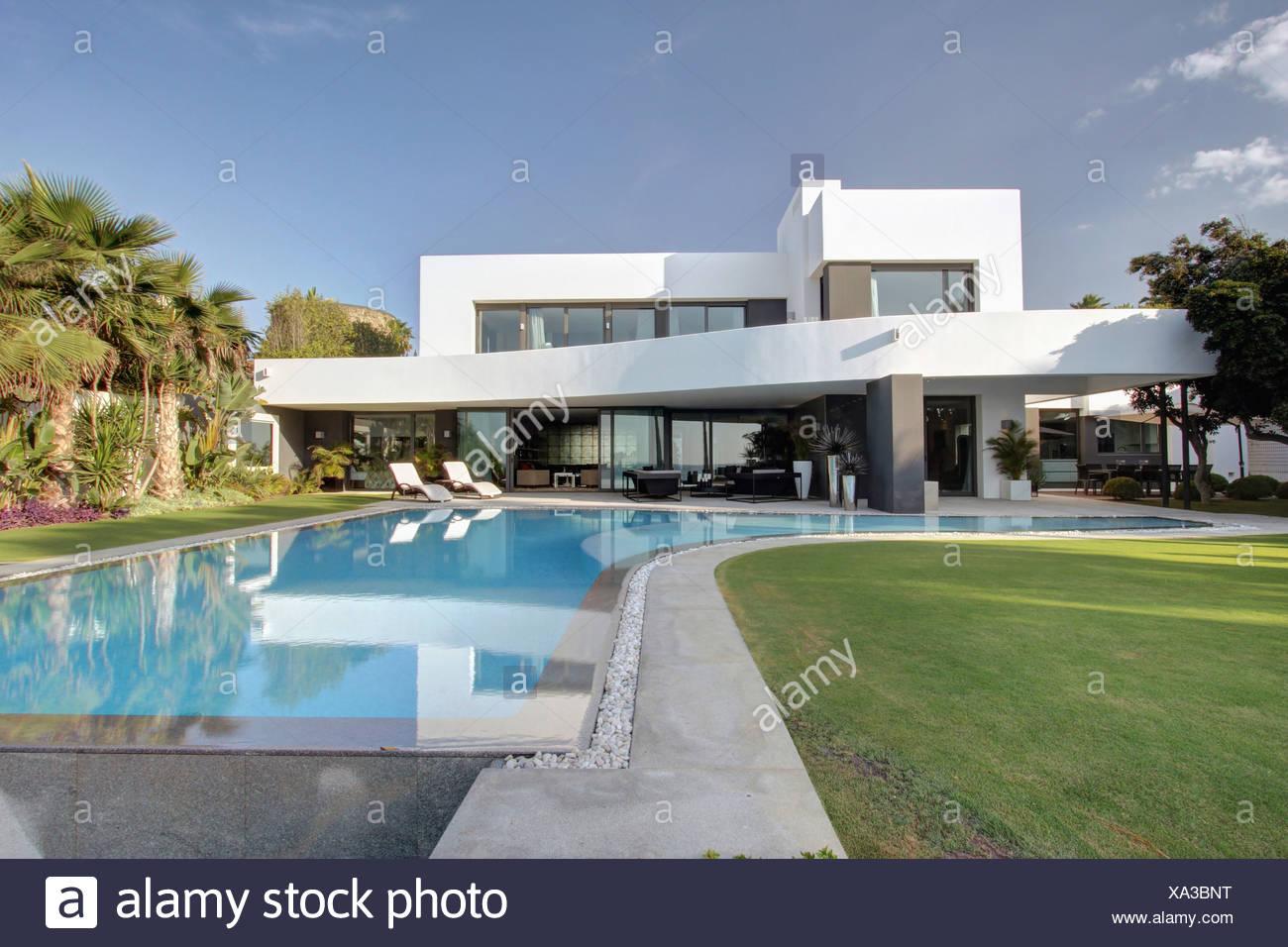Il turchese piscina e prato in un giardino ben curato di for Ville moderne con piscina