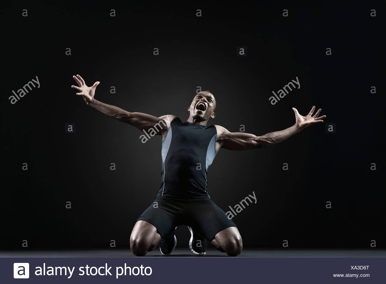 Atleta maschio in ginocchio e grida con disperazione Immagini Stock
