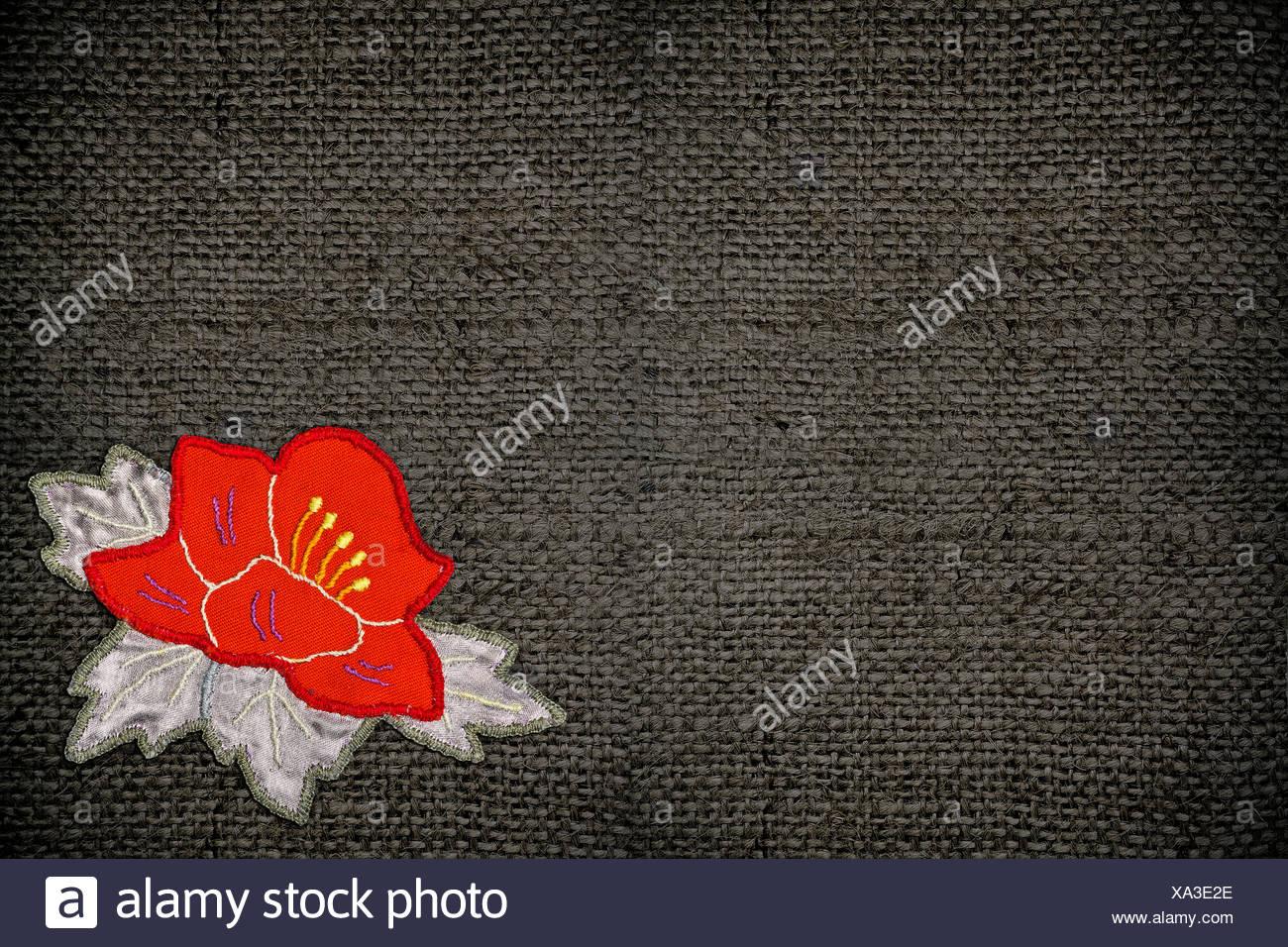 Tessuto grigio con un fiore rosso applique closeup foto & immagine