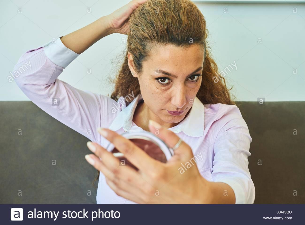 5c5a3905223d Donna matura esaminando il suo volto e la pelle con specchio Immagini Stock