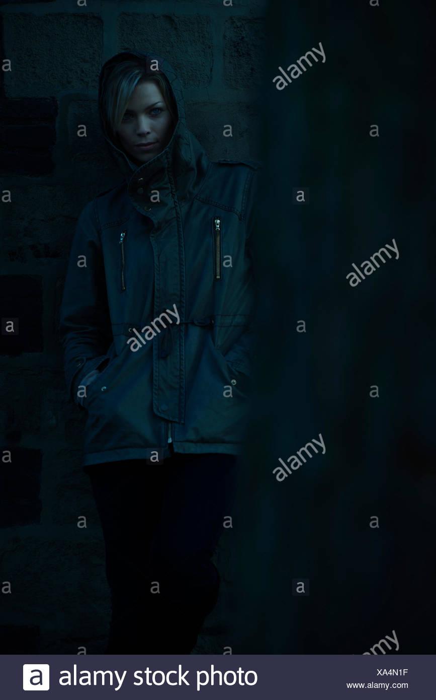 Donna che indossa hooded jacke, appoggiata contro il muro esterno Immagini Stock