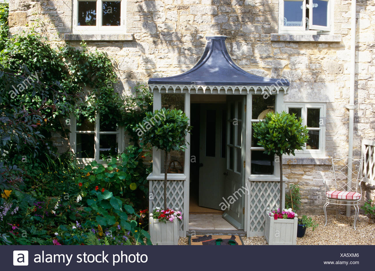 Esterno del cottage in pietra con piante di alloro in fioriere su