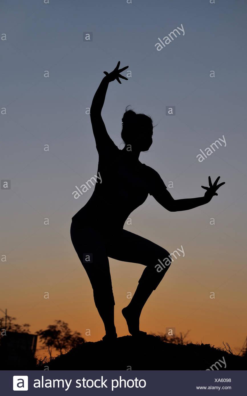 Silhouette della bambina nella danza classica pongono nei pressi di montagna, Pune, Maharashtra Immagini Stock