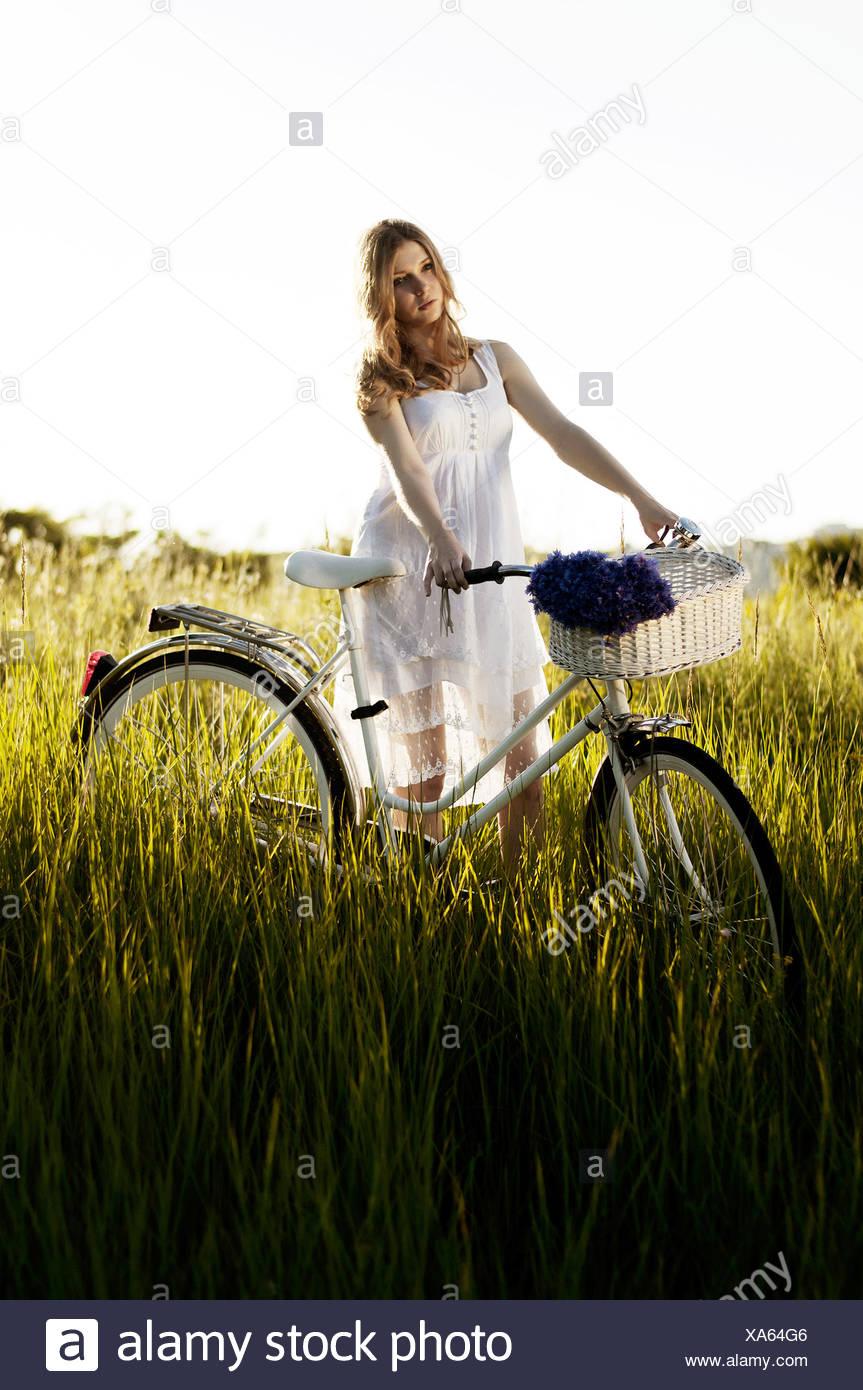 Giovani donne adulte in piedi con la bicicletta Immagini Stock