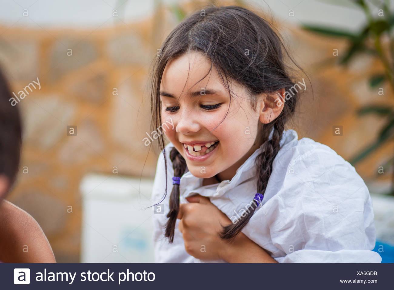 Bambina (6-7) con trecce e camicia bianca a ridere felicemente Immagini Stock