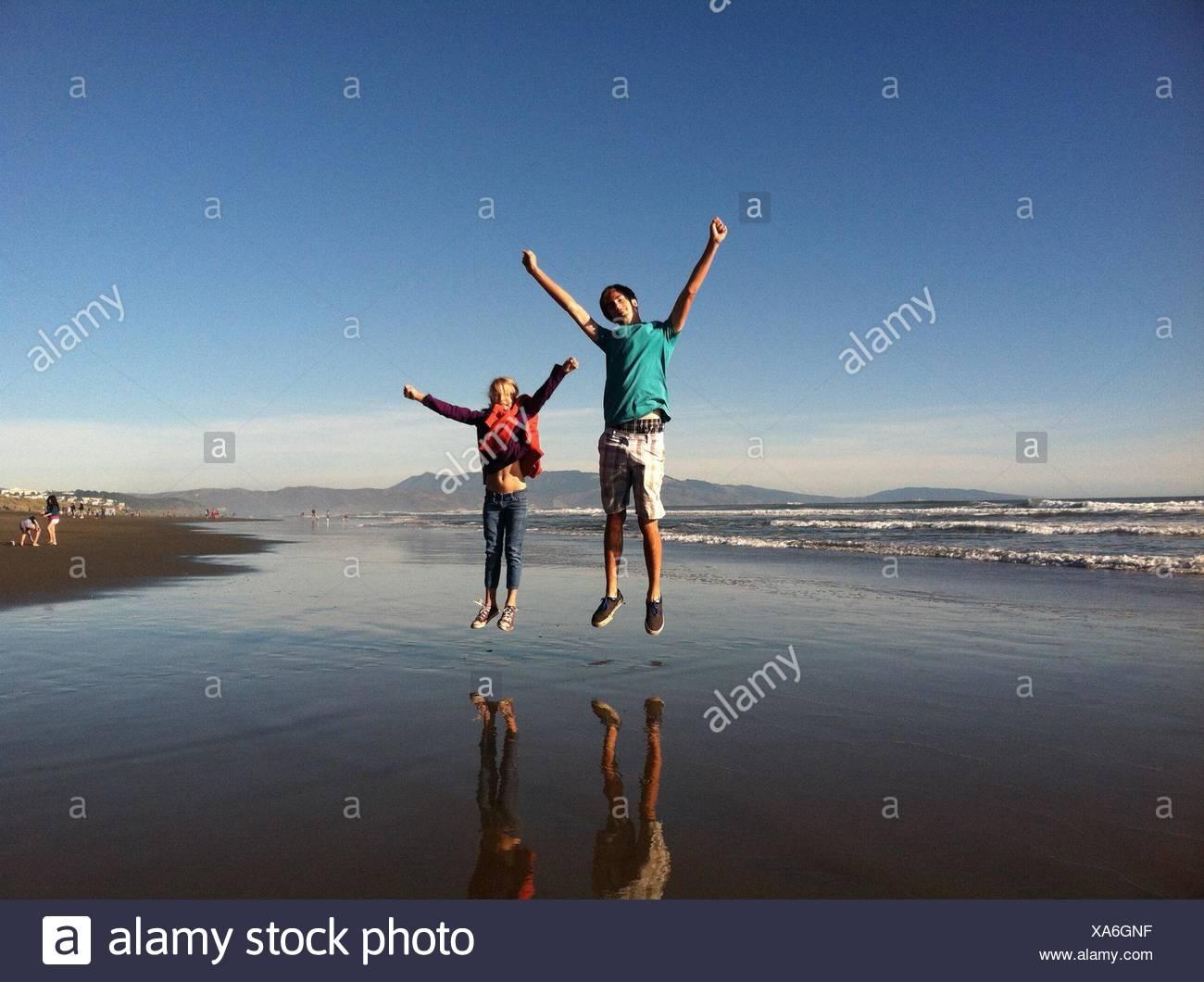 Lunghezza completa di fratello e sorella e saltando al Beach Immagini Stock