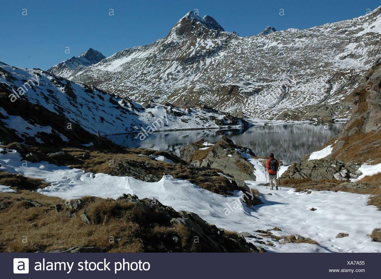 Escursionista, Lago di Dentro, Cadlimo, autunno, neve, Ticino, Svizzera, modello di rilascio, montagne, lago, sul mare Immagini Stock