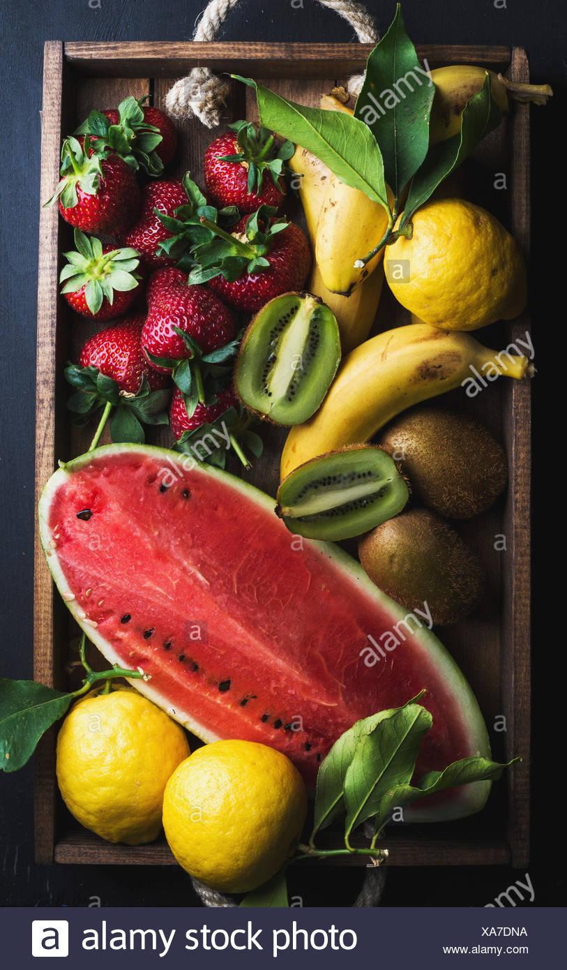 Varie colorata frutta tropicale selezione nel vassoio di legno su sfondo scuro, vista dall'alto. Anguria, fragola, limoni e kiwi Foto Stock