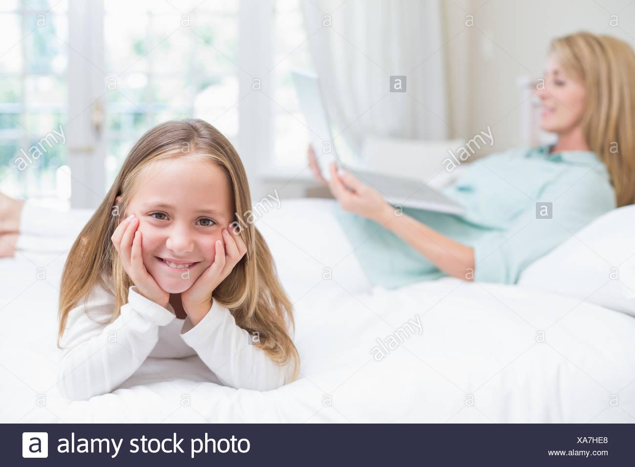 Bambina guardando la fotocamera mentre madre utilizzando laptop Immagini Stock