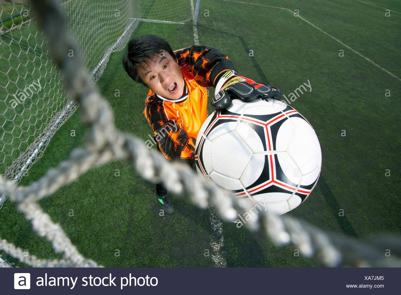 Il portiere la cattura del pallone da calcio Immagini Stock
