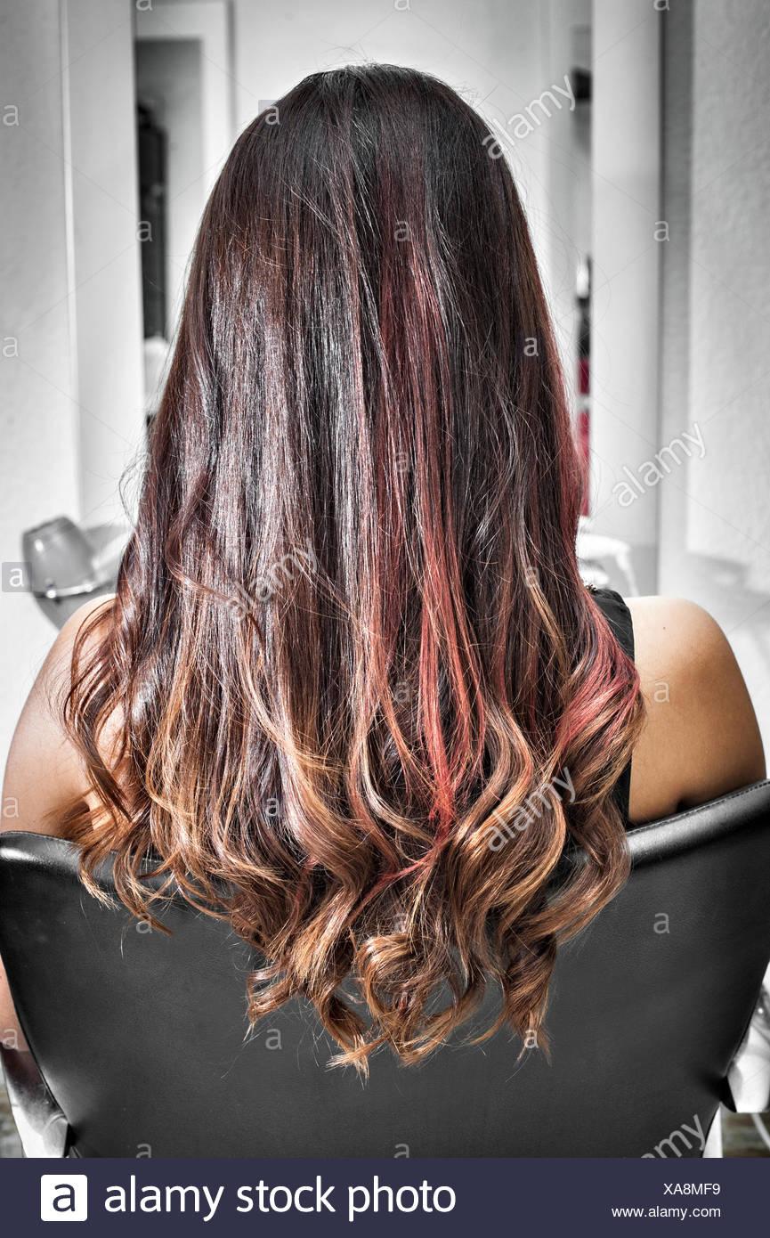 Vista posteriore della giovane donna nel salone di parrucchiere con lunghi brunette capelli con le onde e riflessi rosa Immagini Stock