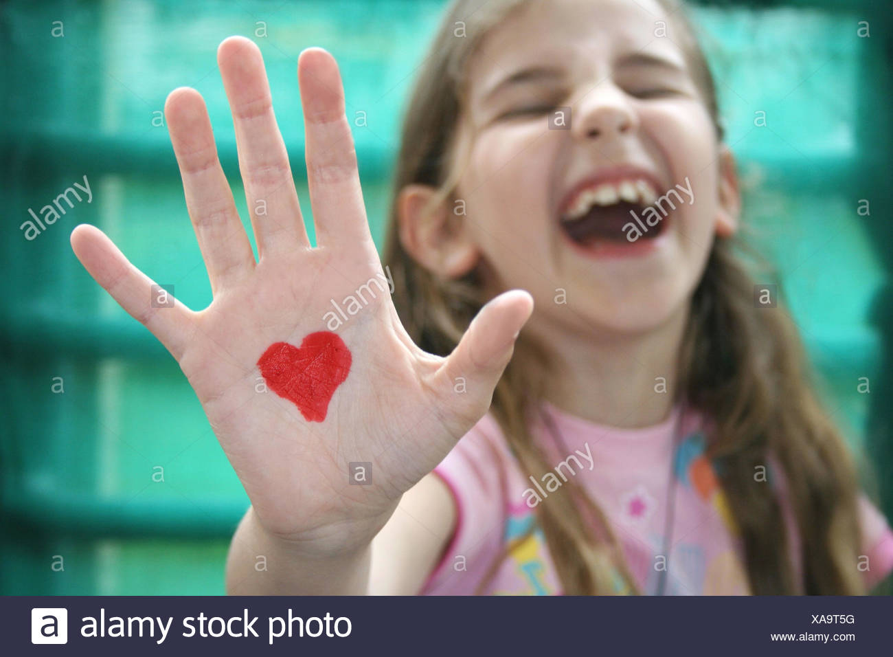 Ragazza con un cuore disegnato sul palmo della sua mano Immagini Stock