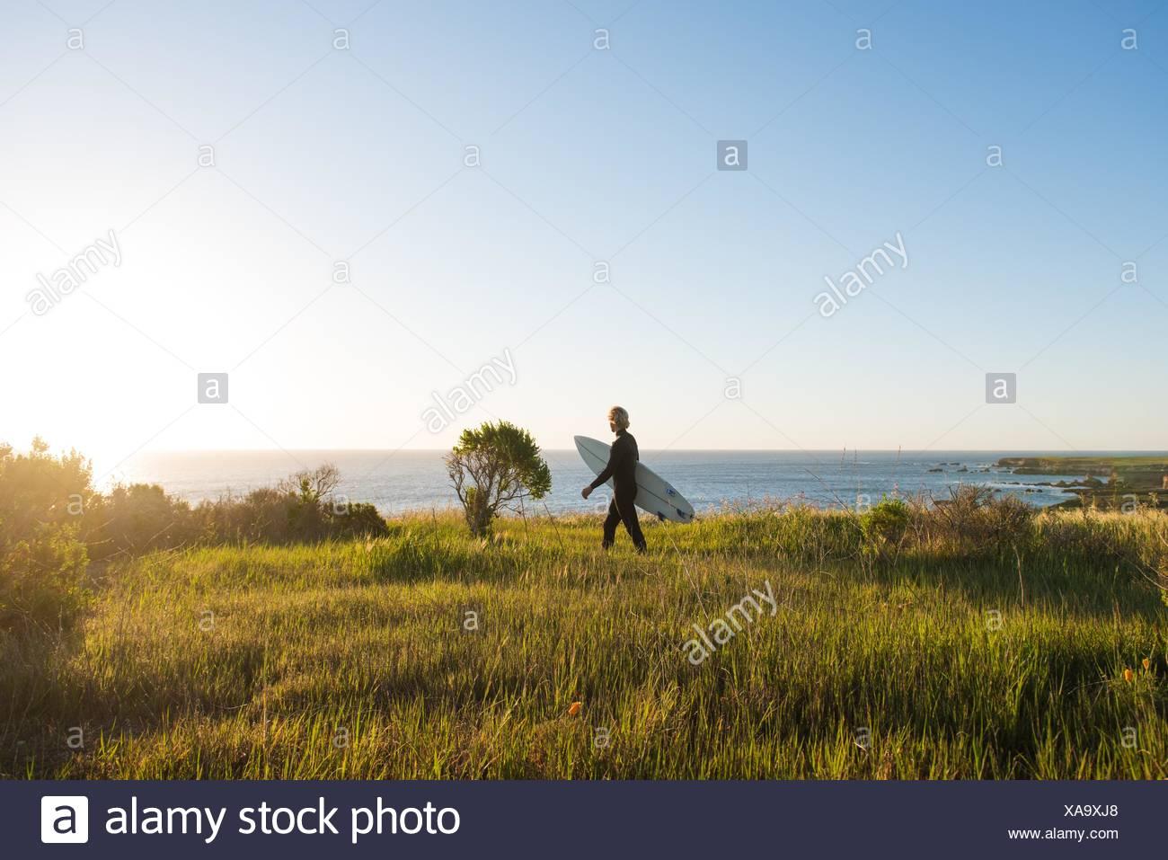 Giovane maschio surfer a piedi con la tavola da surf di sunrise Immagini Stock