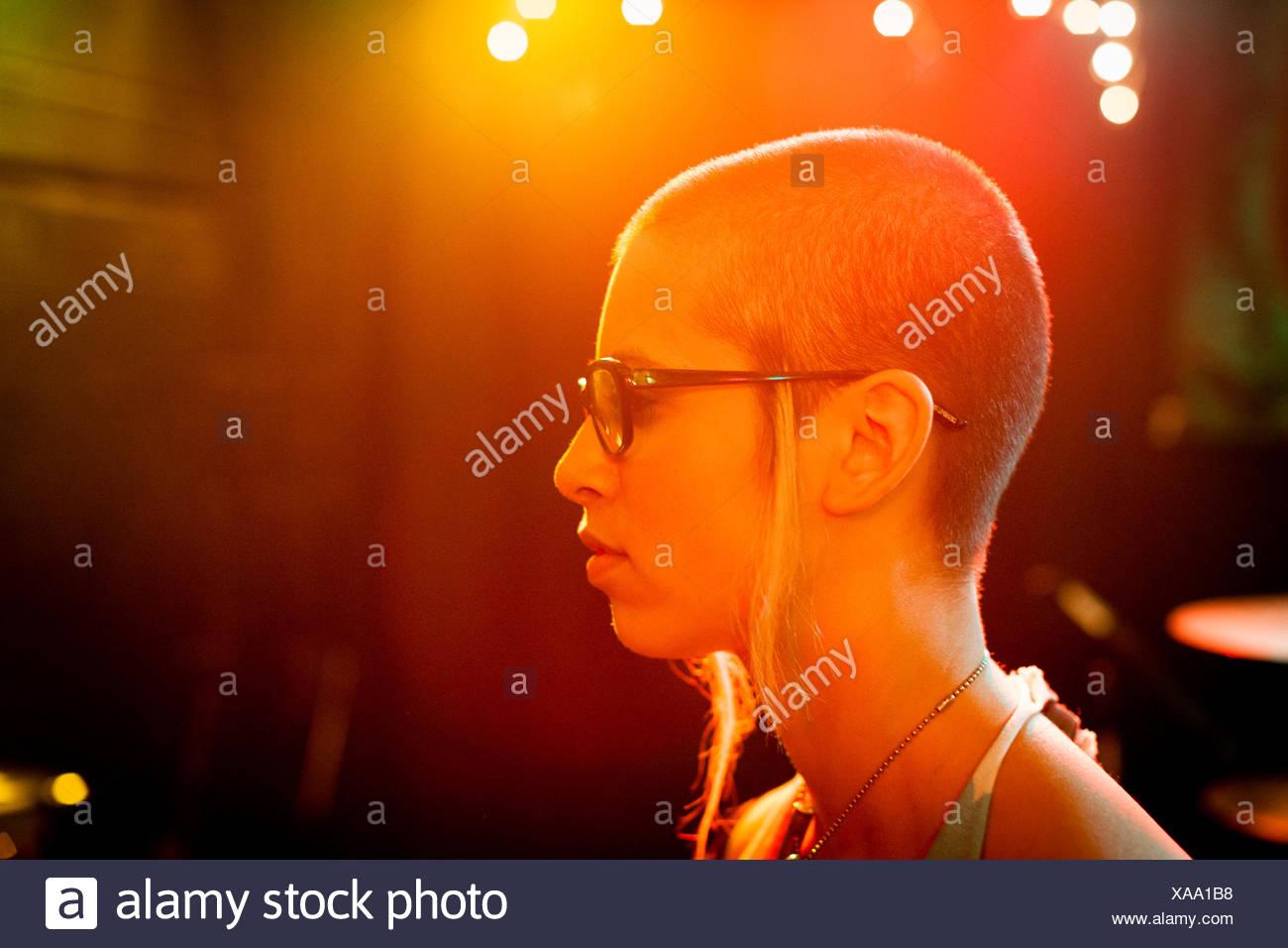 Profilo della ragazza punk, vestita di nero bordati di occhiali Immagini Stock