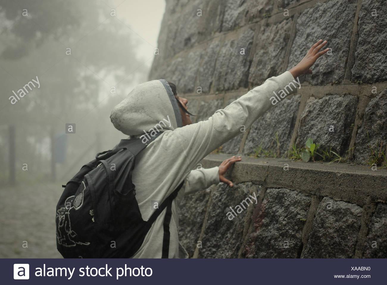 Adolescente di toccare la parete di pietra Immagini Stock