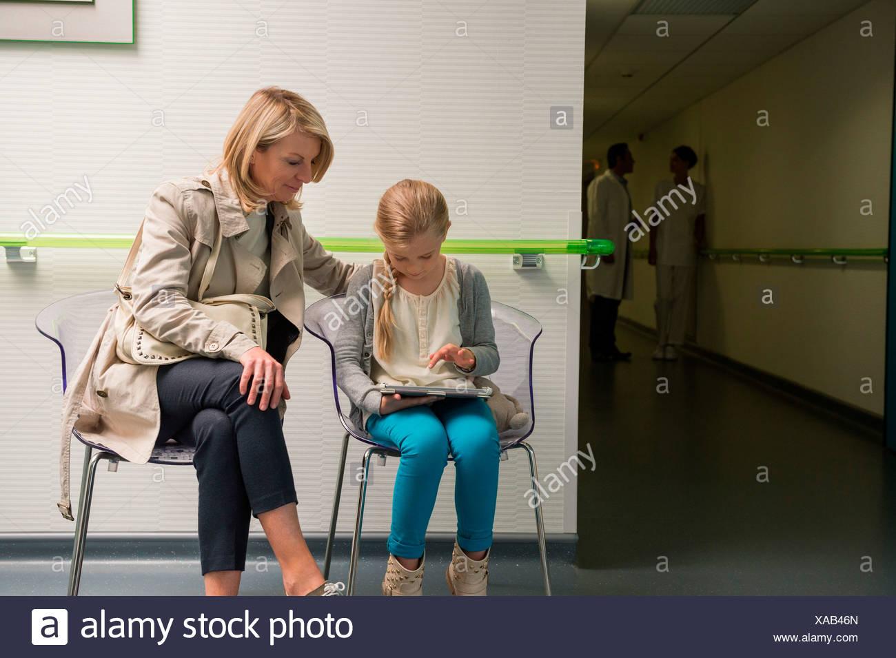 Donna con sua figlia seduta in ospedale in sala d'attesa Immagini Stock