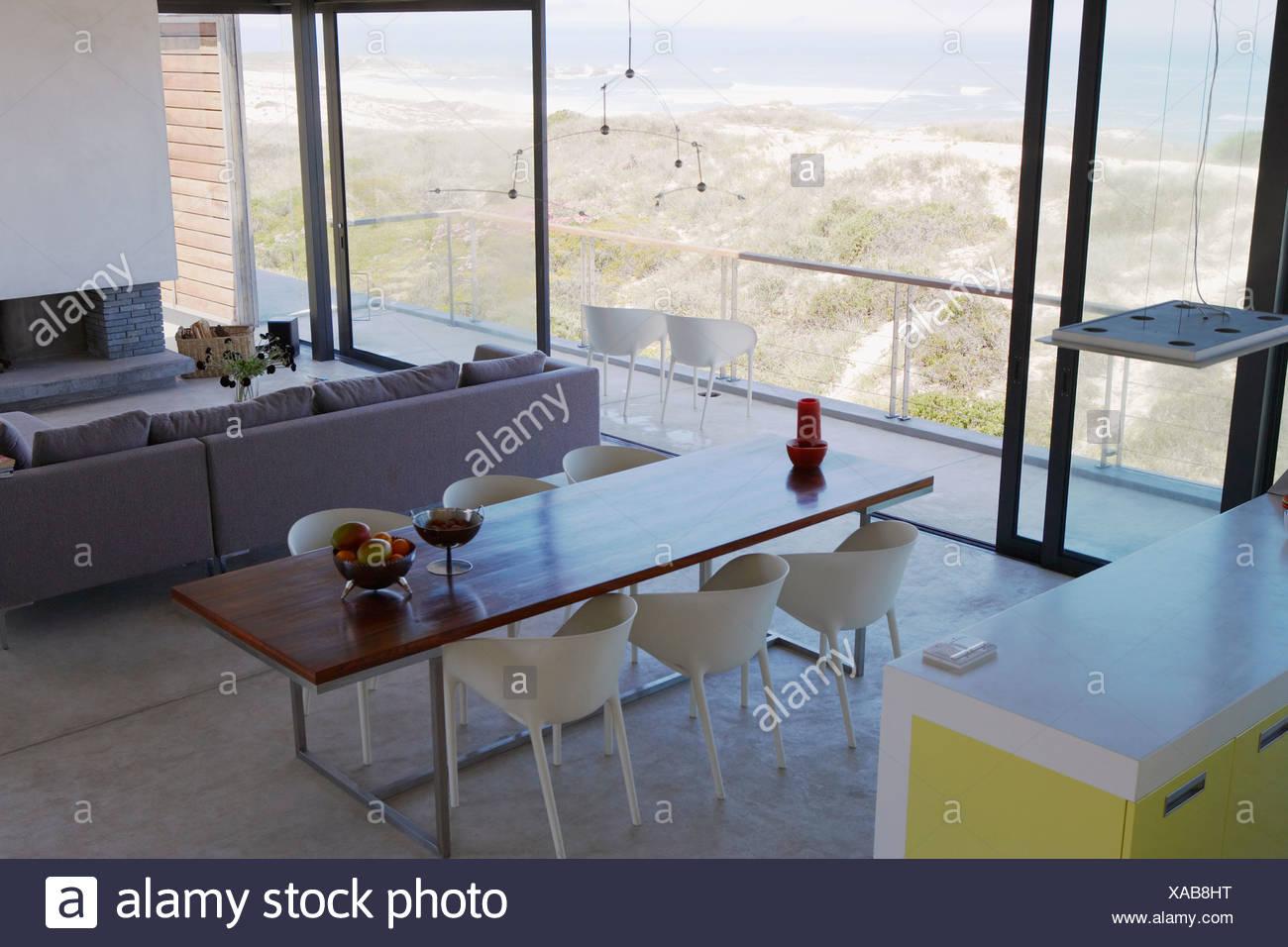 Soggiorno e sala da pranzo con grandi finestre e vista di sabbia e ...