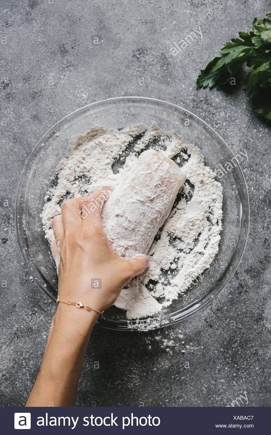 Passo 1/4 una donna è il rivestimento di un filetto di pesce con la farina. Immagini Stock