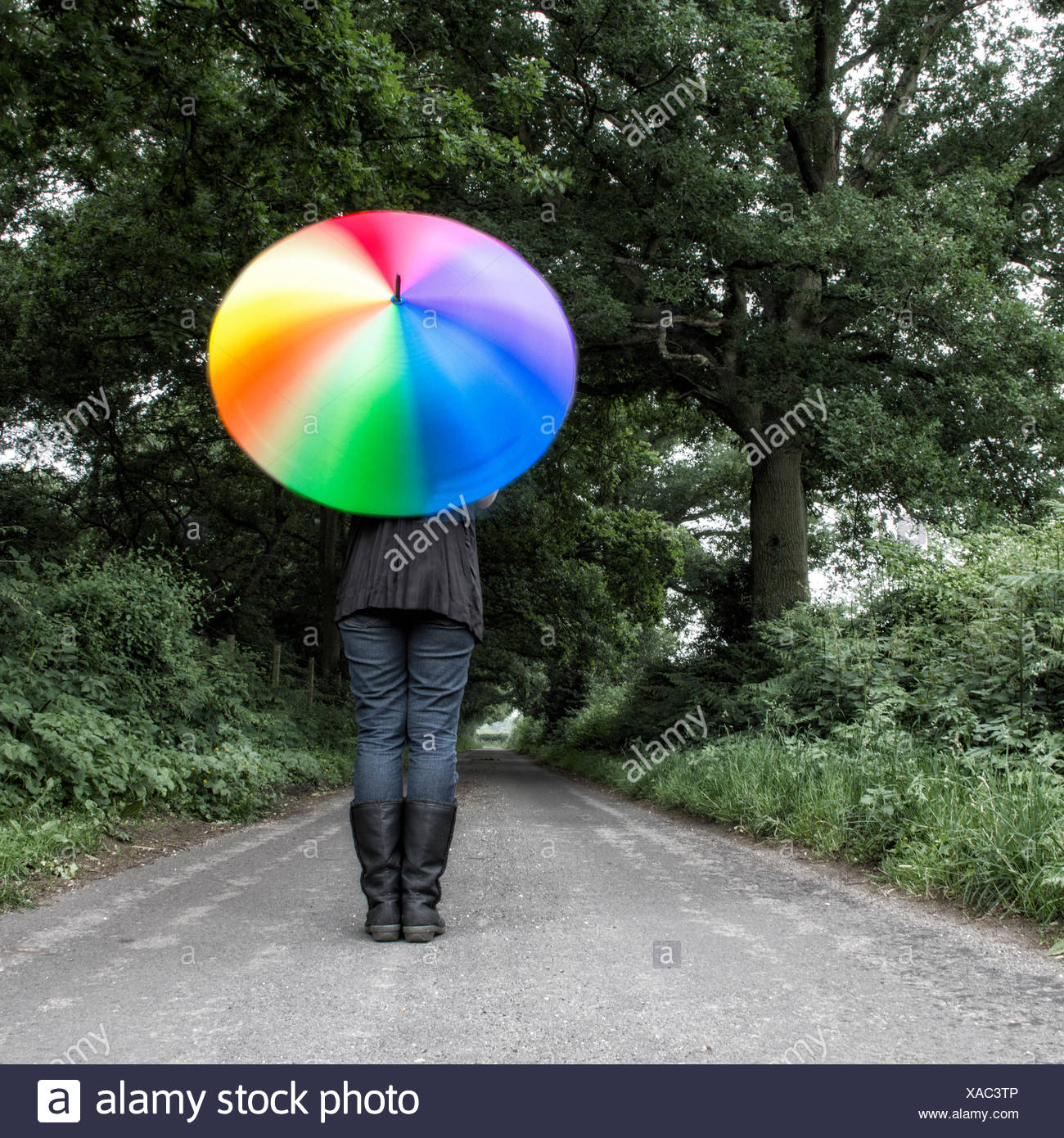 Donna in piedi in strada la filatura multi-ombrello colorato Immagini Stock