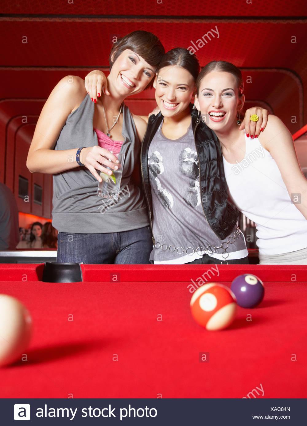 Tre donne in piedi da tavolo da biliardo sorridente Immagini Stock