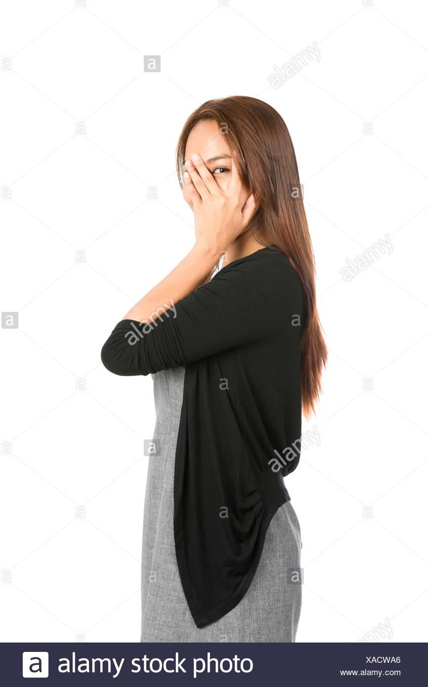 Mano che ricopre la faccia occhio Peeking dito donna asiatica Immagini Stock