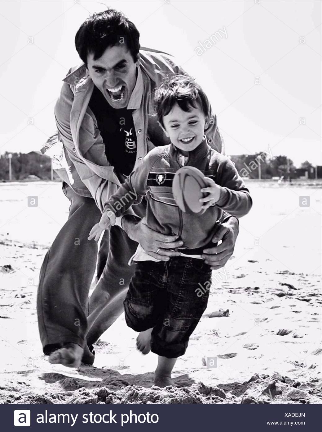 Padre giocando a rugby gioco con il figlio sulla spiaggia Immagini Stock
