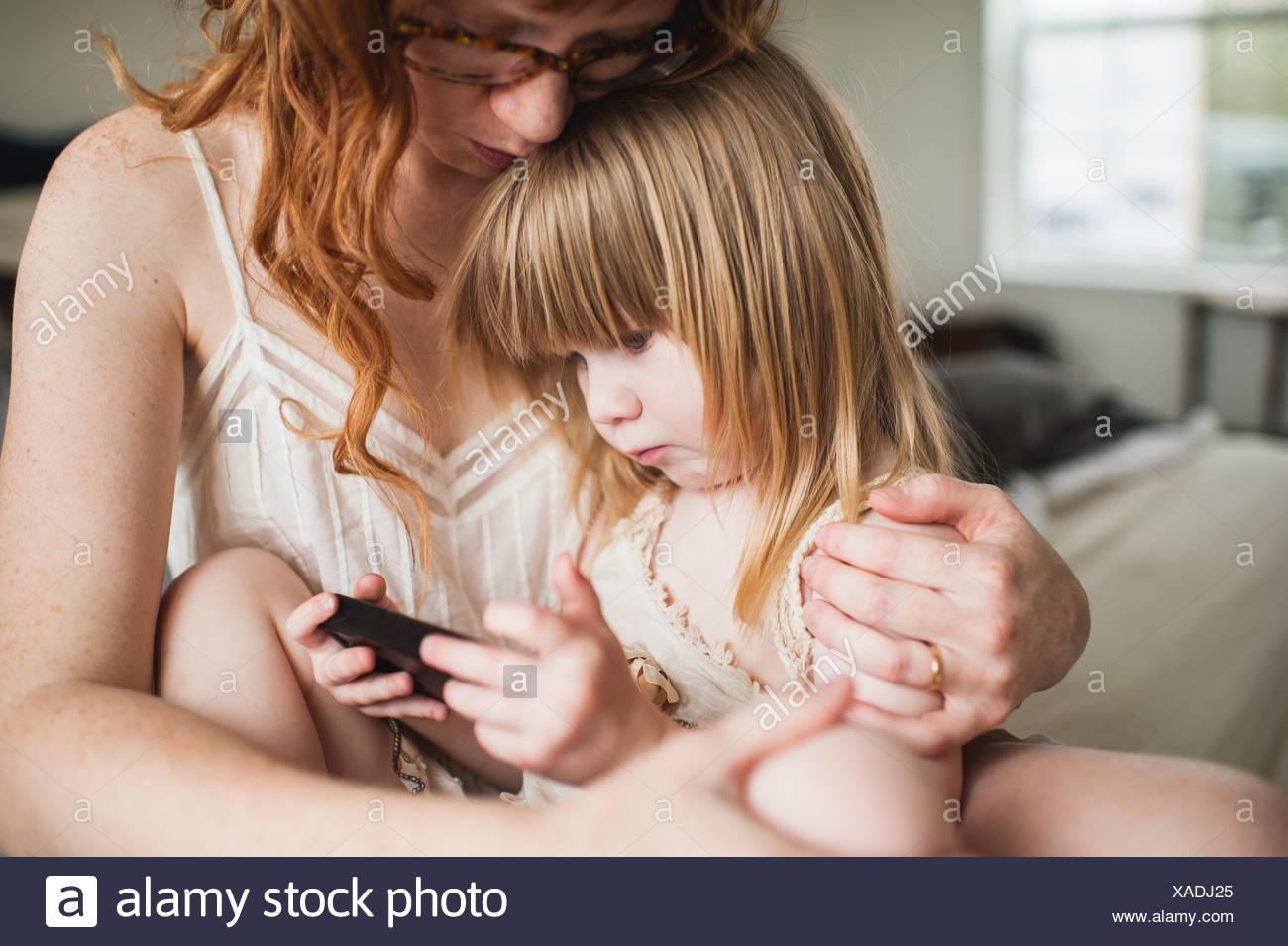 La madre abbraccia la figlia, utilizza lo smartphone Immagini Stock