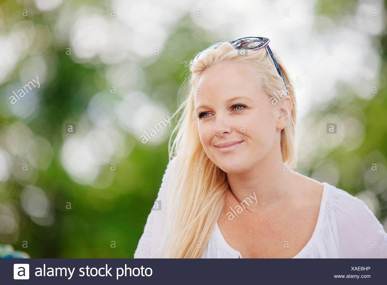 Ritratto di capelli lunghi giovane donna bionda con occhiali da sole sulla testa guardando lontano sorridente Immagini Stock