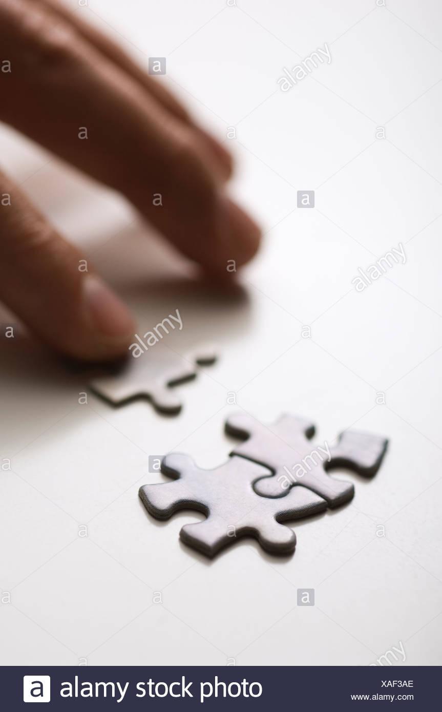 Mano umana unire pezzi di puzzle, close-up Immagini Stock