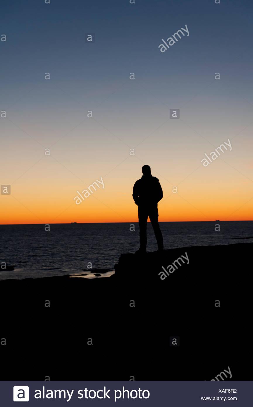 La Svezia, Bohuslan, Silhouette di un uomo in piedi sulla spiaggia al tramonto Immagini Stock