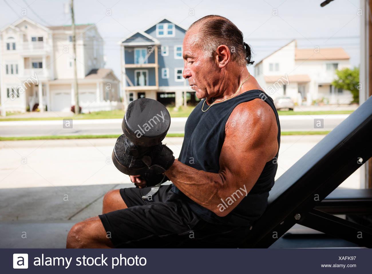 Ritratto di senior muscolare uomo muto di sollevamento campane Immagini Stock