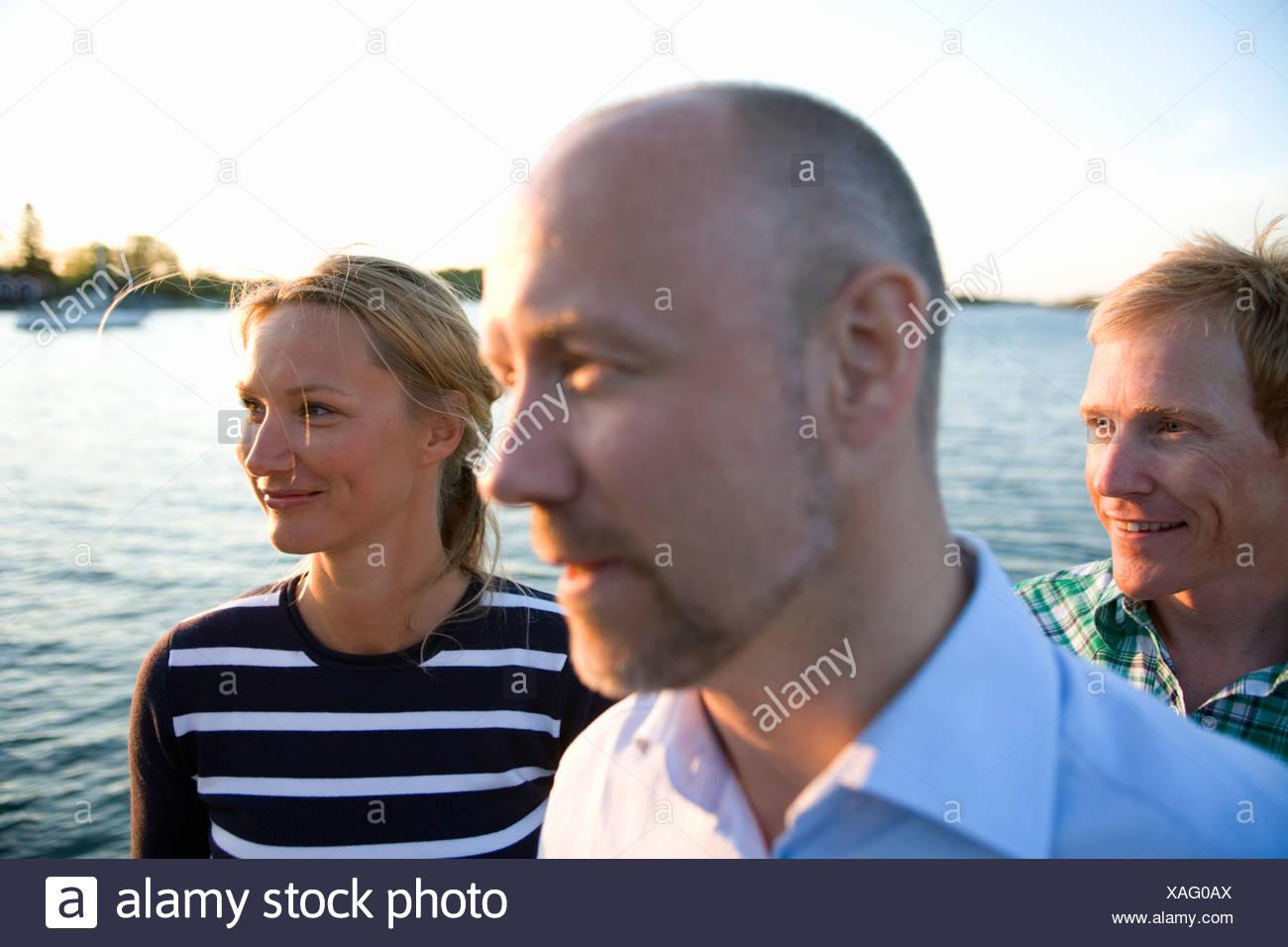 Tre persone in piedi dall'acqua, Fejan, arcipelago di Stoccolma, Svezia. Foto Stock