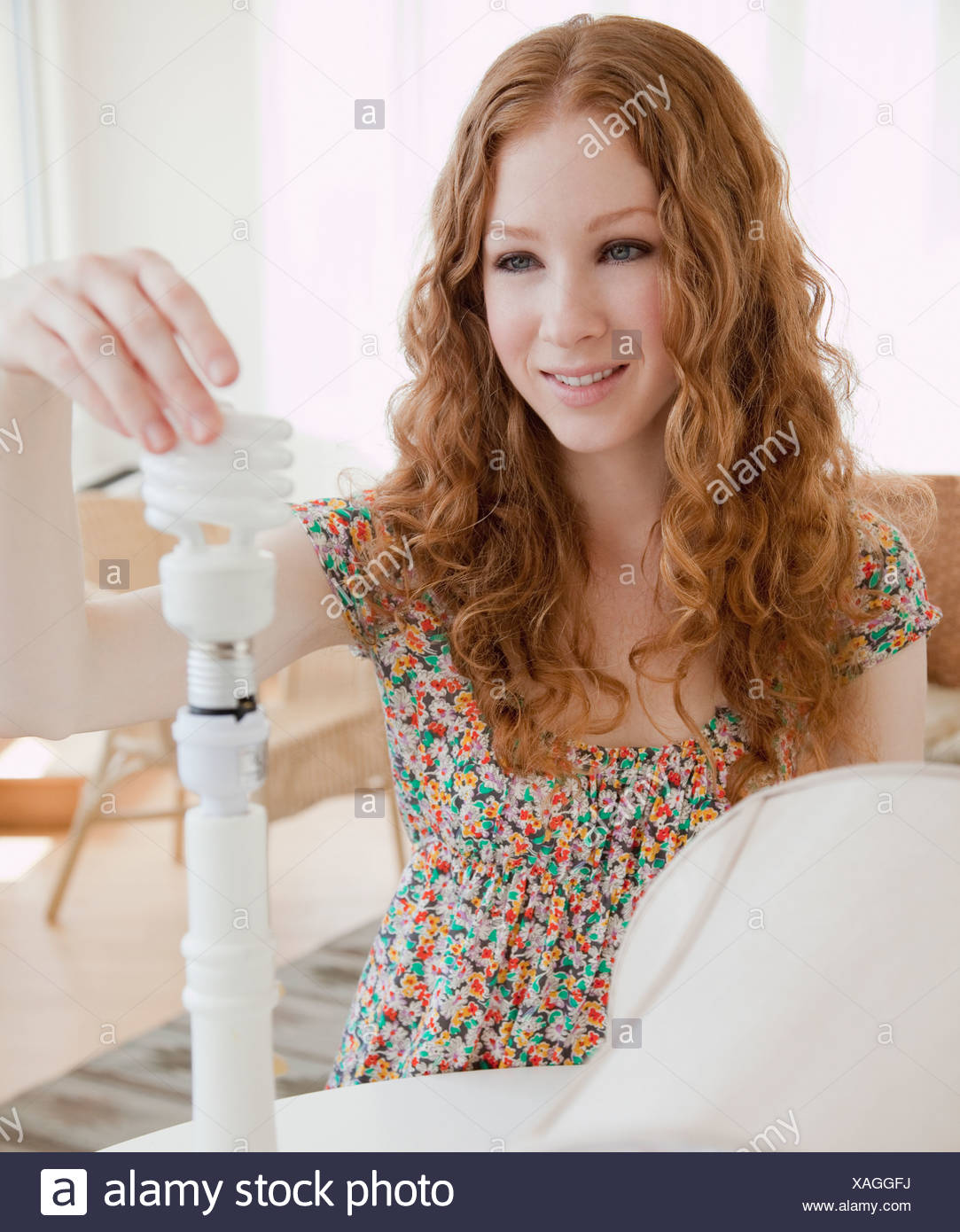 Donna avvitando la lampadina Immagini Stock