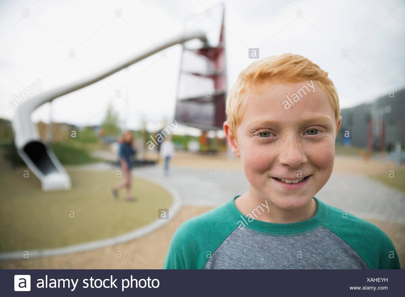 Close up ritratto sorridente ragazzo capelli rossi parco giochi Immagini Stock