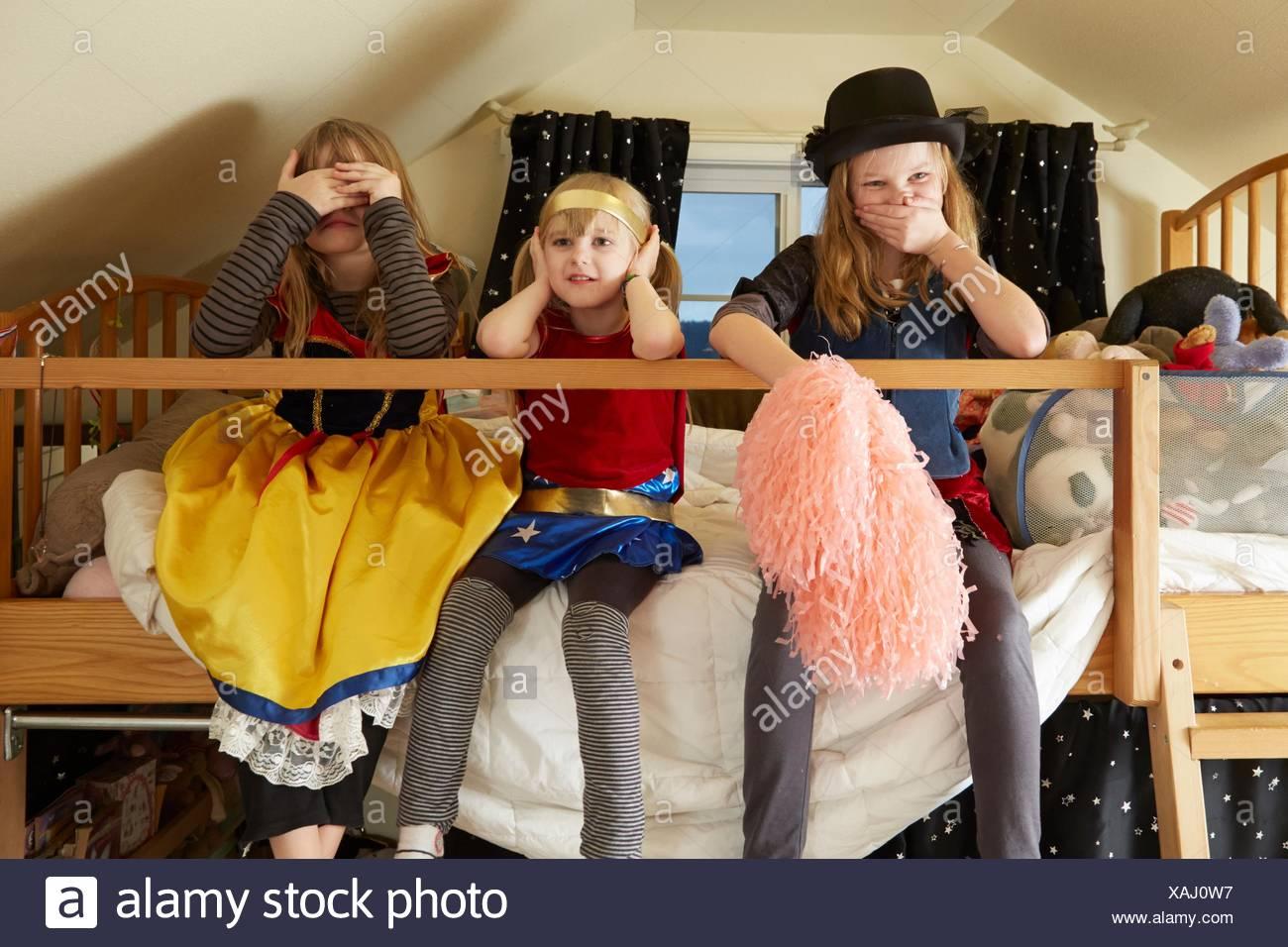 Le tre sorelle, seduta sul letto, indossando abiti fantasiosi costumi, che copre la bocca e le orecchie e gli occhi Immagini Stock