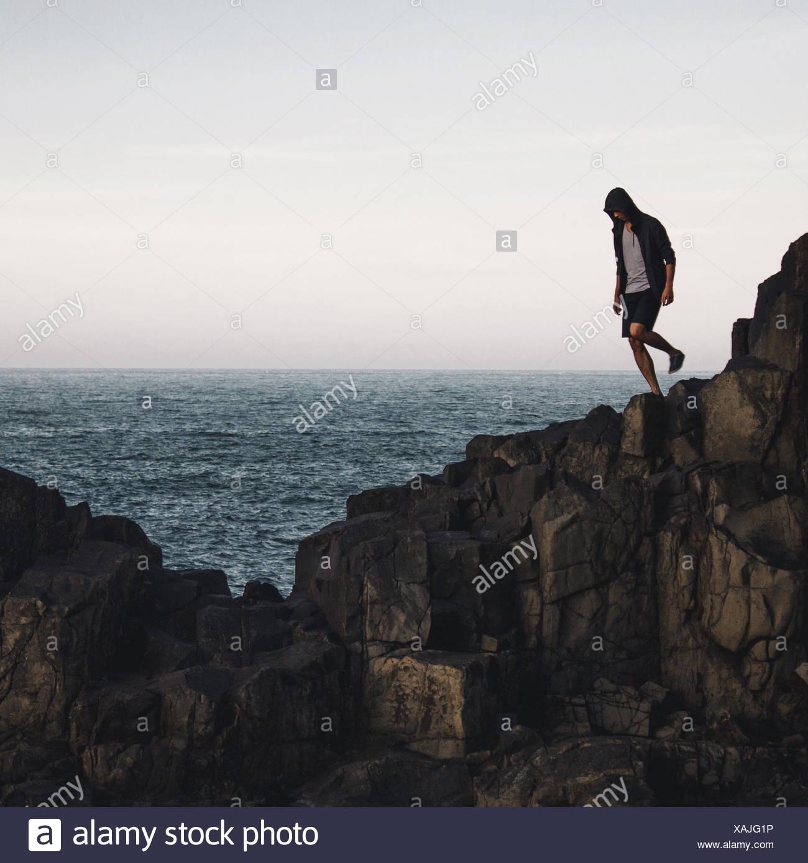 Uomo in piedi sulla scogliera dal mare contro Sky Immagini Stock