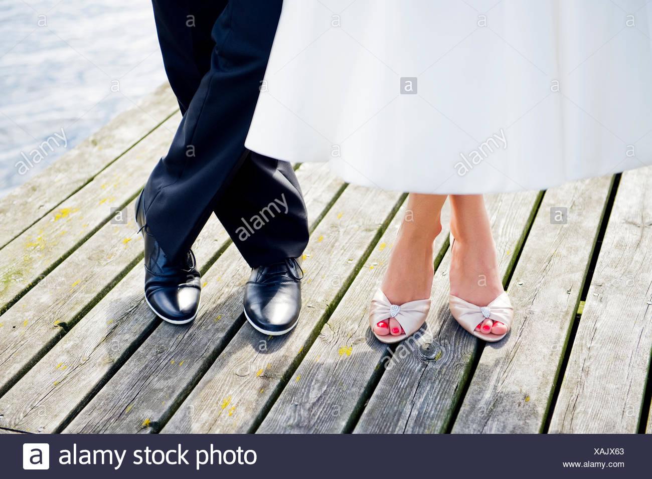 La Svezia, Uppland, Arholma, i piedi di un uomo e di una donna in piedi sul molo in legno Immagini Stock