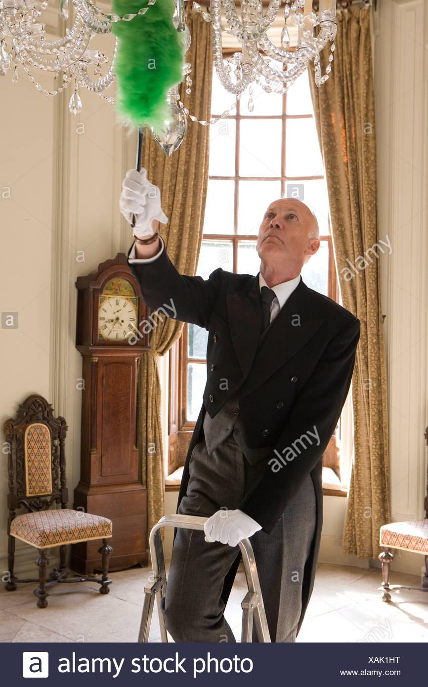 Il maggiordomo sulla scaletta spolvero lampadario Immagini Stock