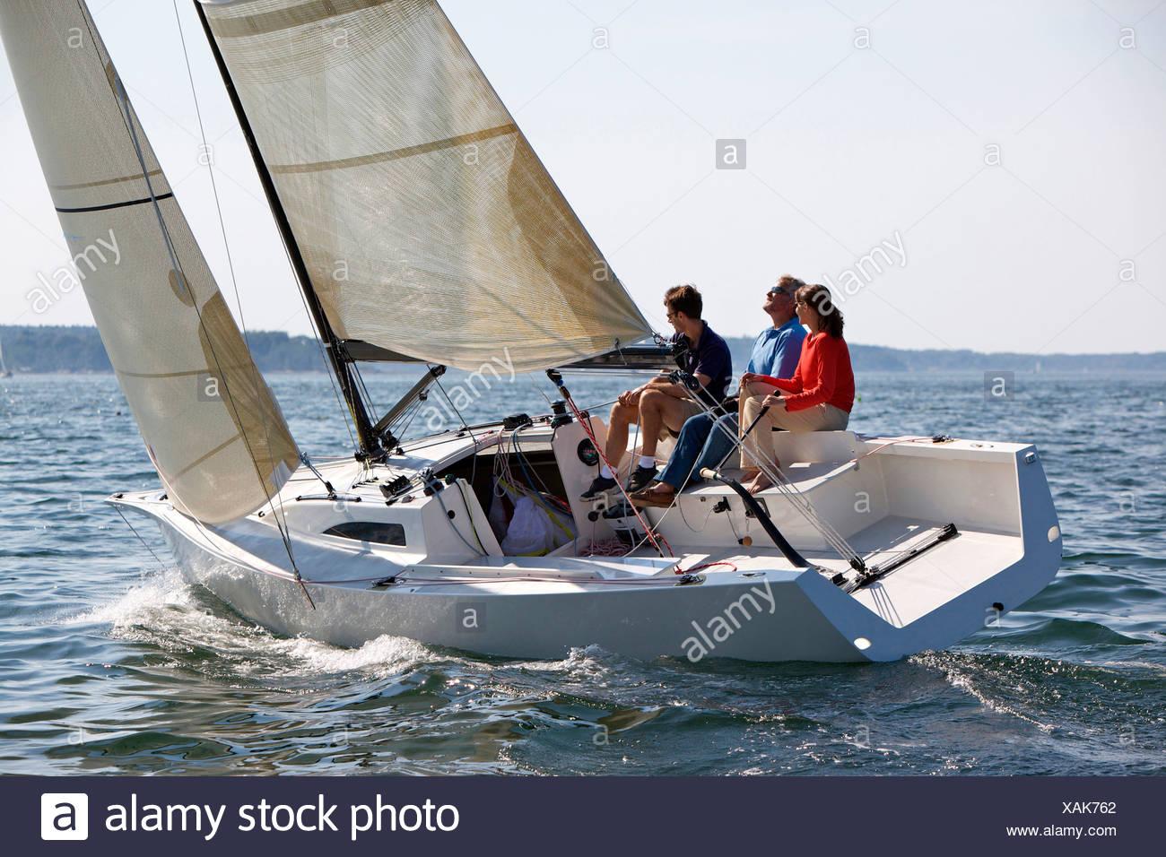 Tre adulti godendo una giornata di sole a bordo di un daysailer sul Casco Bay, Maine. Immagini Stock