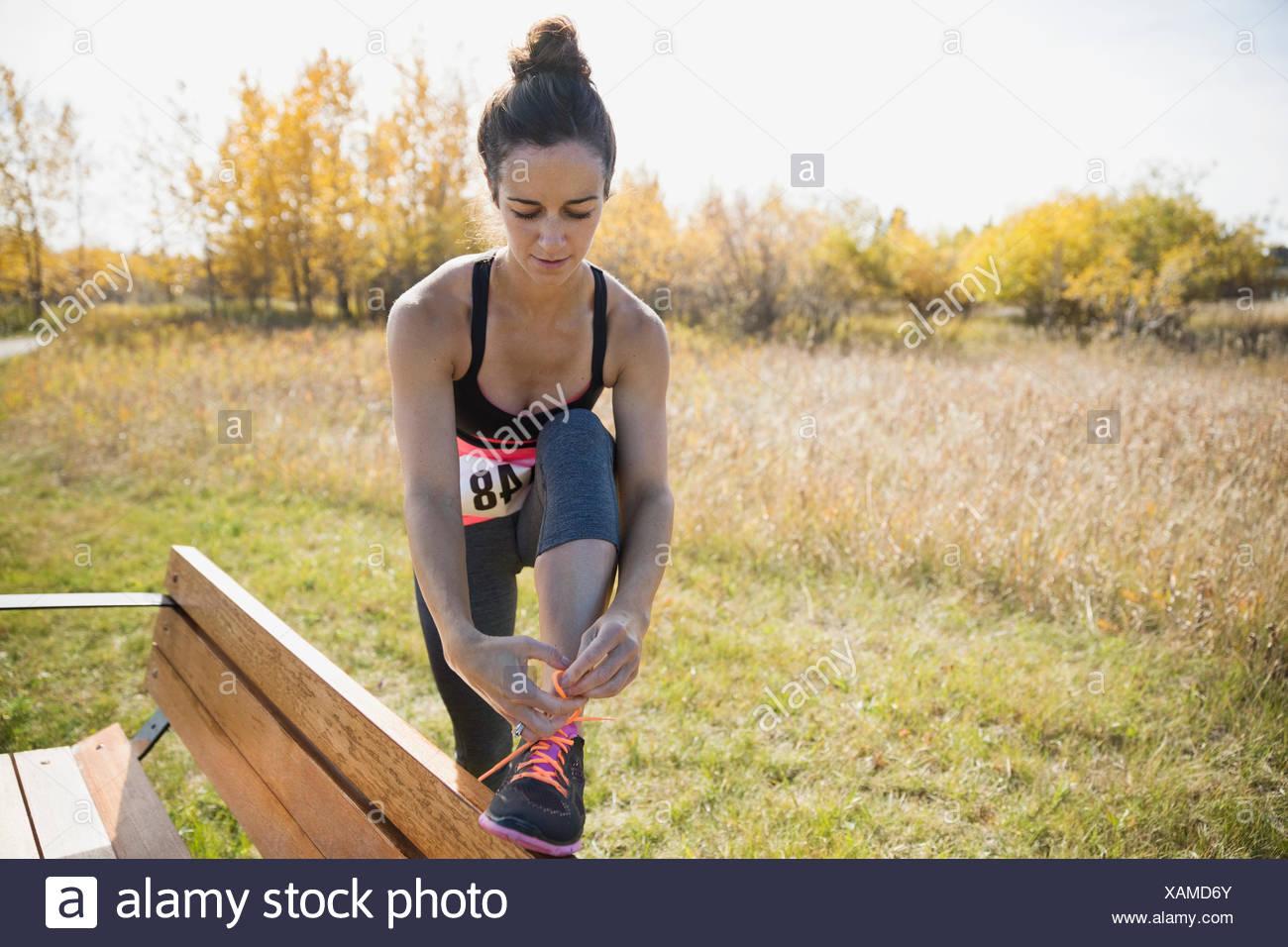 Pareggiatore scarpa di legatura su una panchina nel parco Immagini Stock
