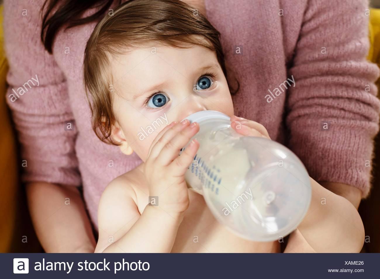 Baby boy bere latte dalla bottiglia Immagini Stock