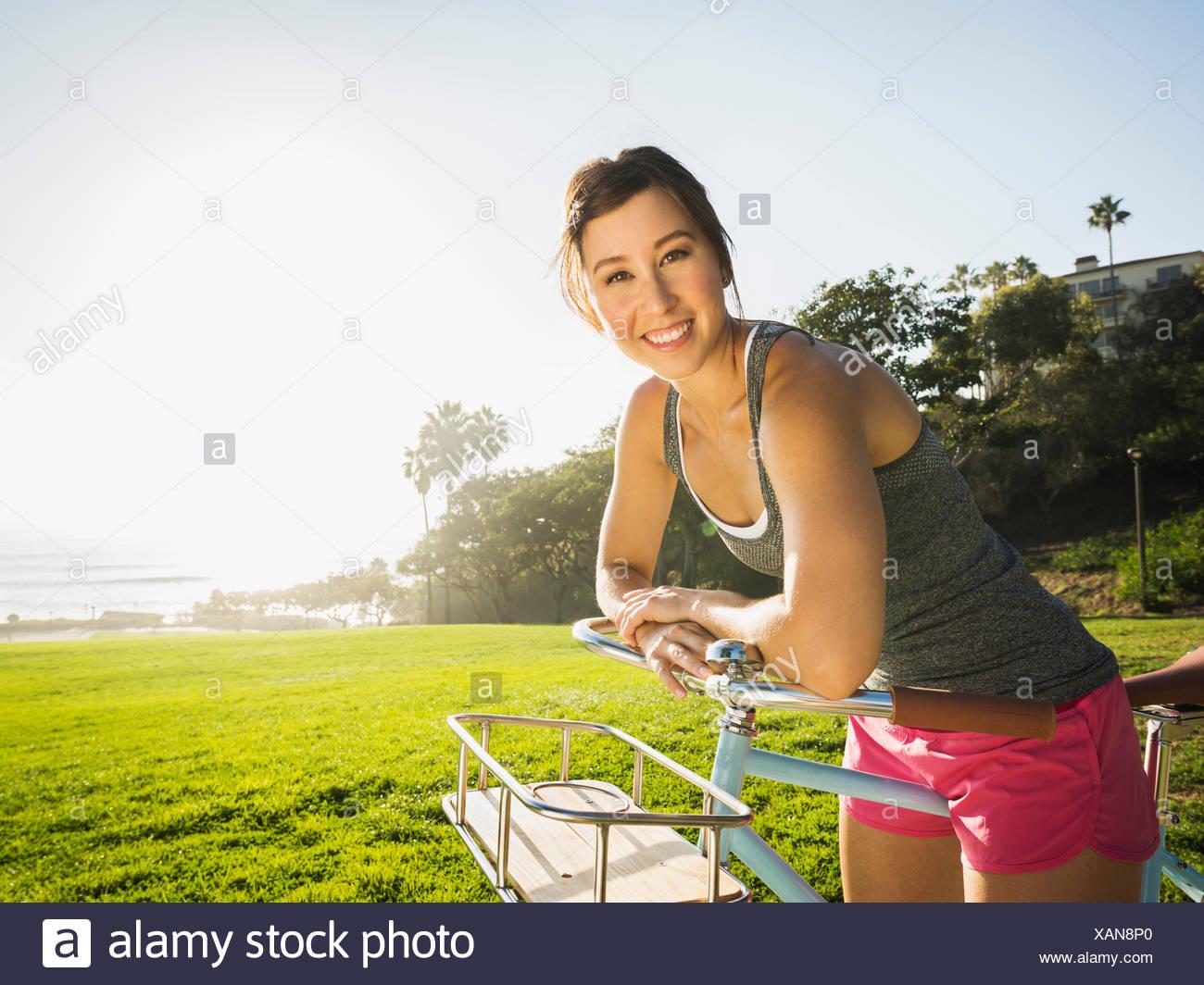 Giovane donna con la bicicletta in posizione di parcheggio Immagini Stock