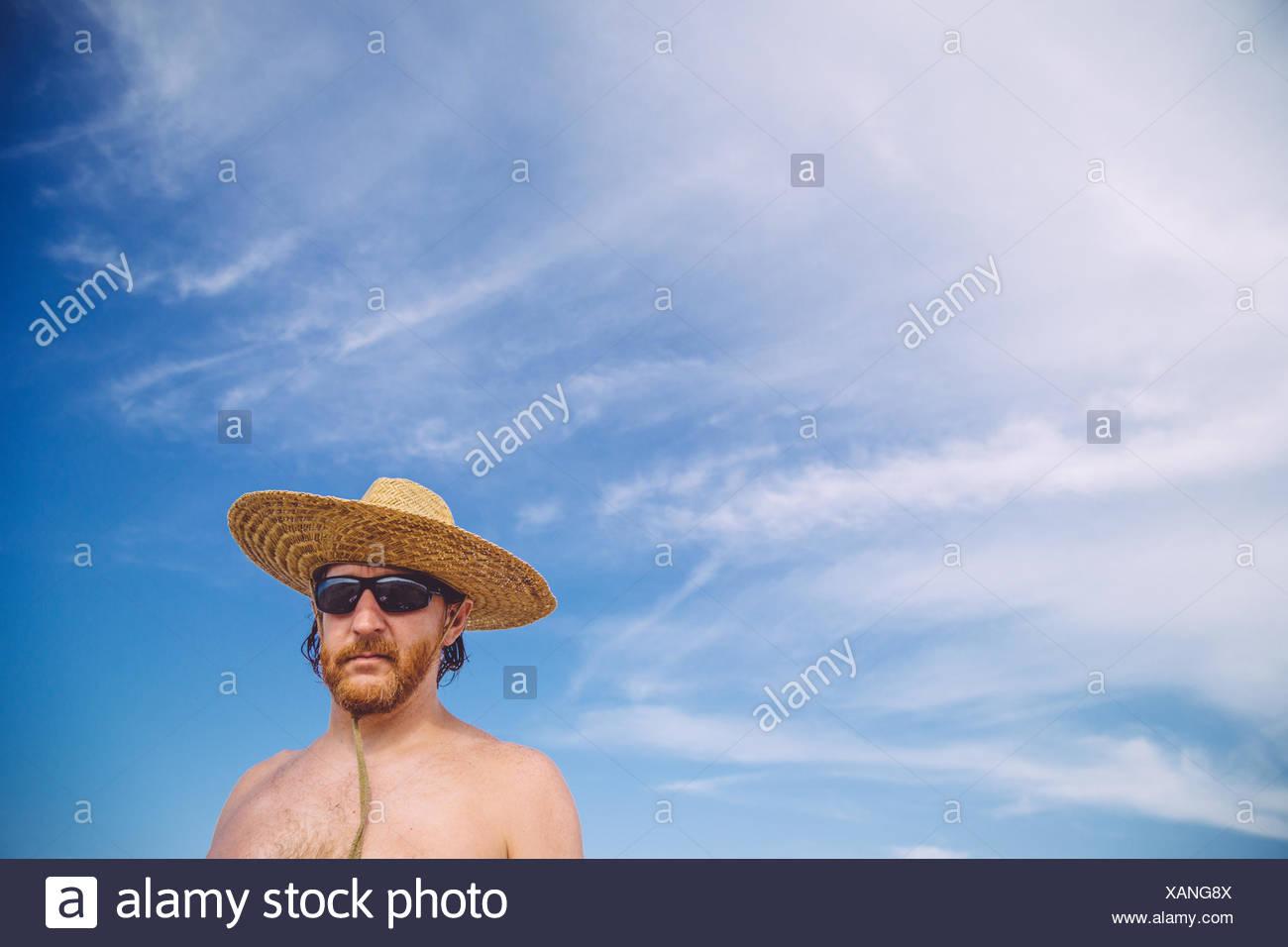 Basso angolo di vista Shirtless uomo maturo indossando Hat contro Sky Immagini Stock