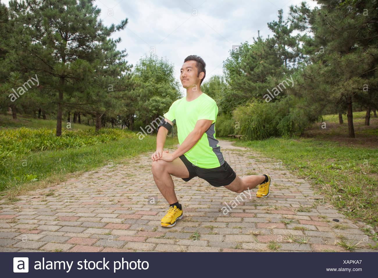 Giovane maschio runner stretching gambe in posizione di parcheggio Immagini Stock