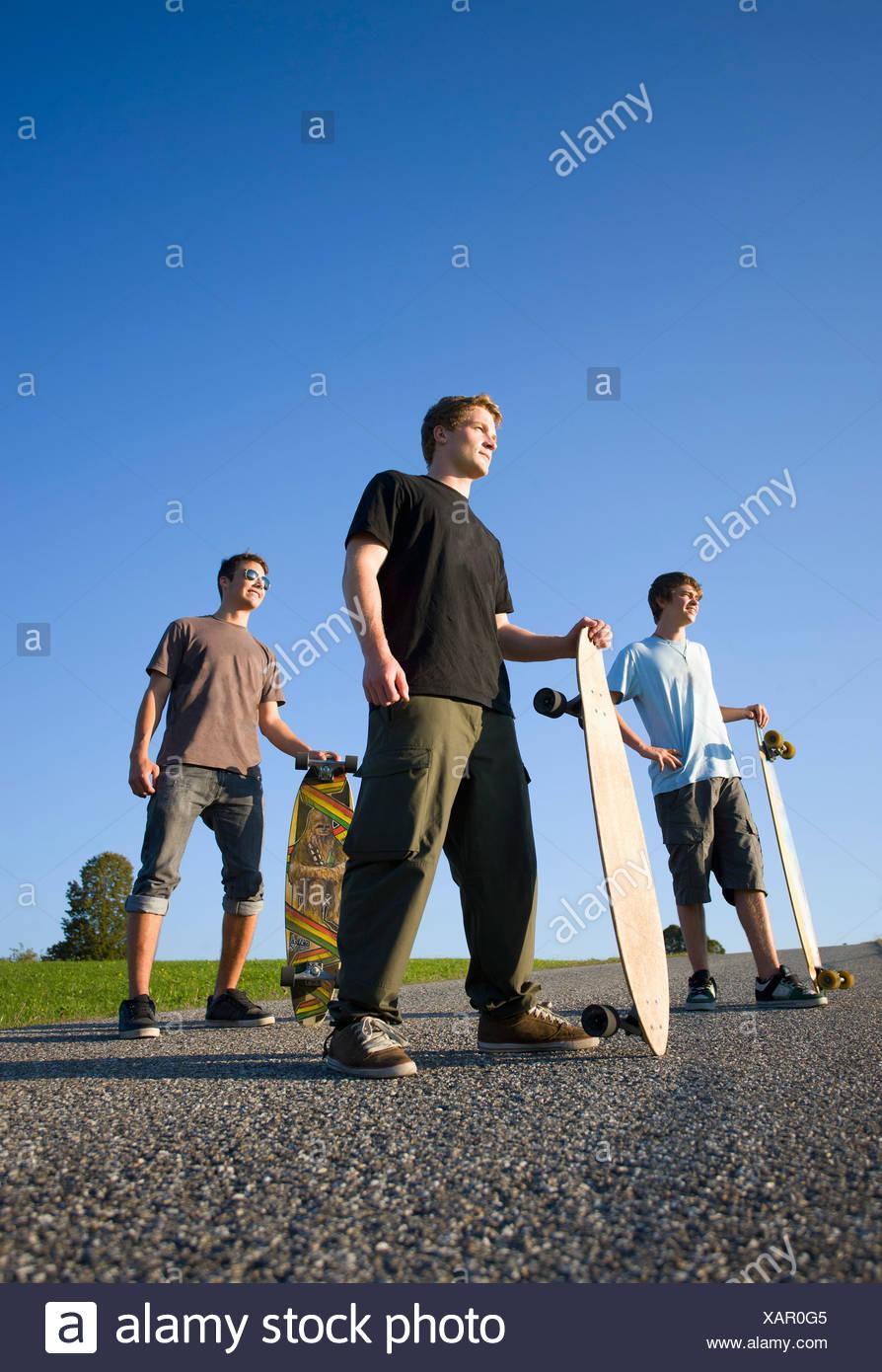 Austria, giovani uomini con lo skateboard su strada Immagini Stock