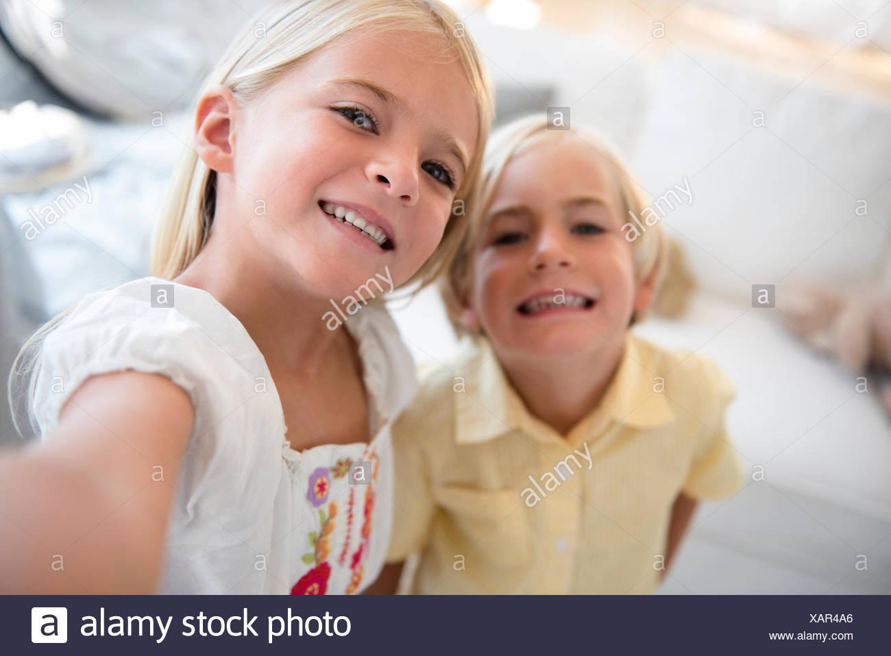 La ragazza (6-7) e ragazzo (4-5) guardando la fotocamera Immagini Stock