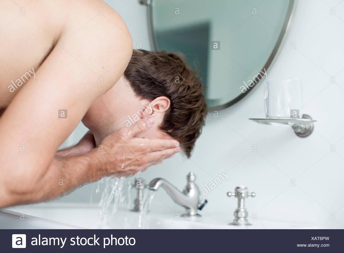 L'uomo faccia il lavaggio nel lavandino del bagno Immagini Stock
