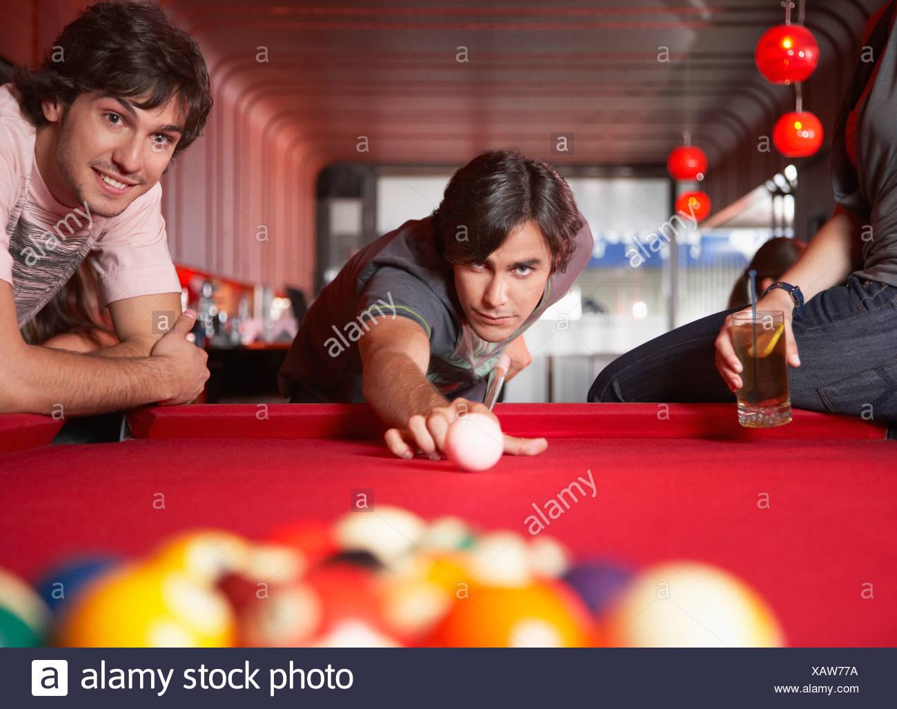 Tre persone con bevande giocando a biliardo e sorridente Immagini Stock