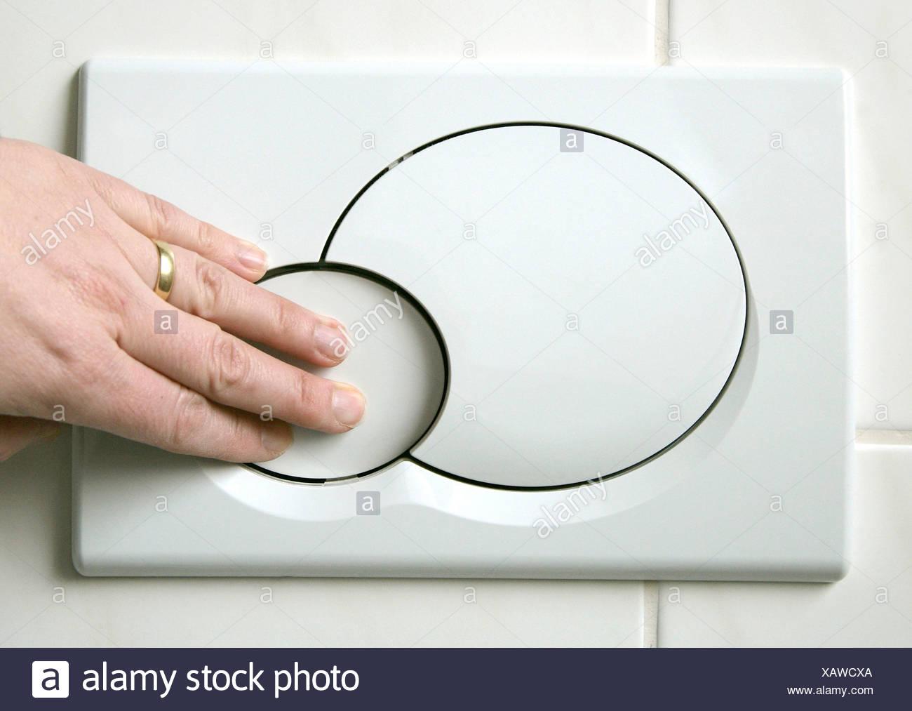 Mano che spinge il basso pulsante di scarico su un pulsante di due